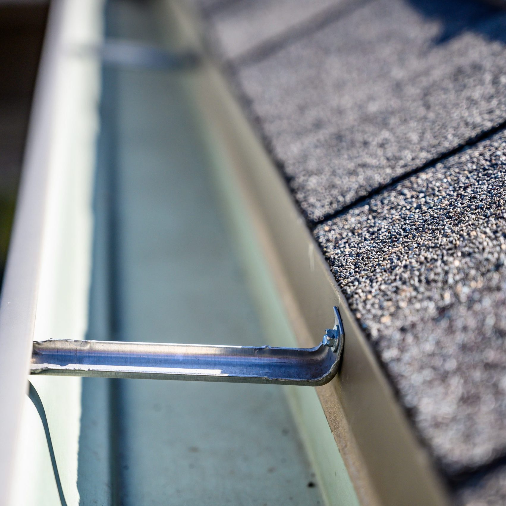 view inside roof gutter with clips and edge of shingles